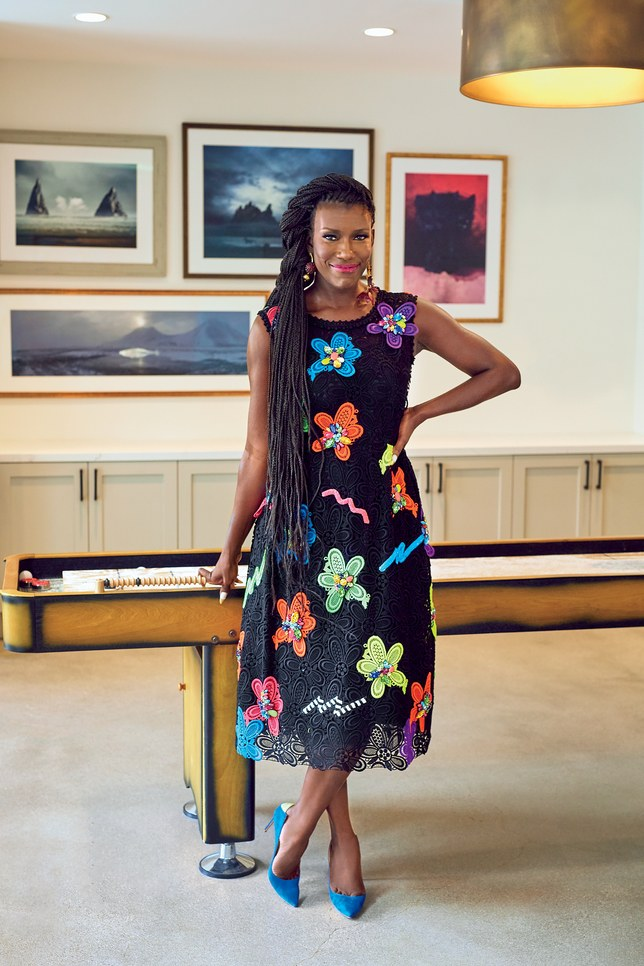 Woman standing in front of pool table, wearing floral dress