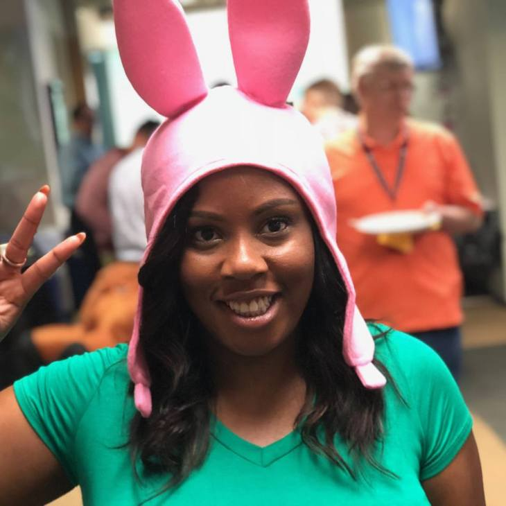 Woman holding up a peace sign, wearing pink bunny ears