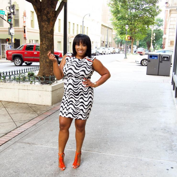 A black woman smiling, wearing a black and white dress, standing on street with hand on hip